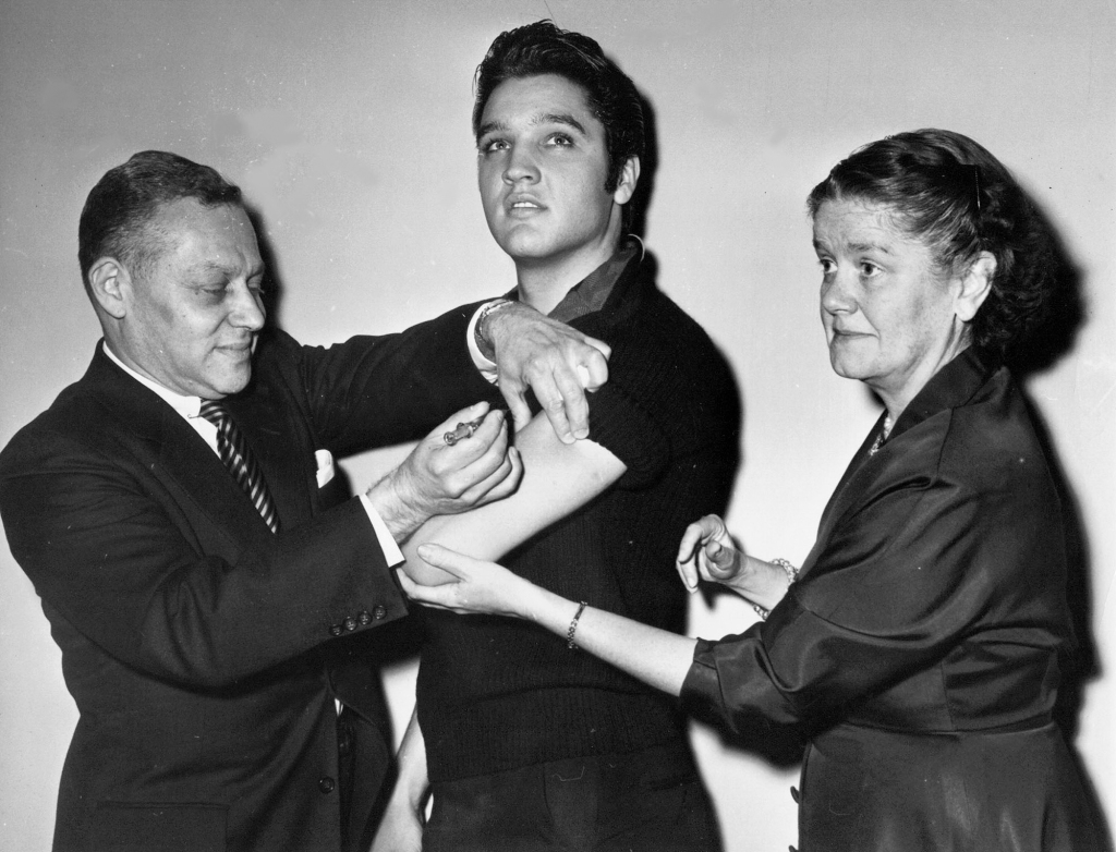 In this Oct. 28, 1956 file photo, Elvis Presley receives a Salk polio vaccine shot in New York City from Dr. Harold Fuerst, left. At right is Dr. Leona Baumgartner, commissioner of the New York City health department. (AP Photo/File)2